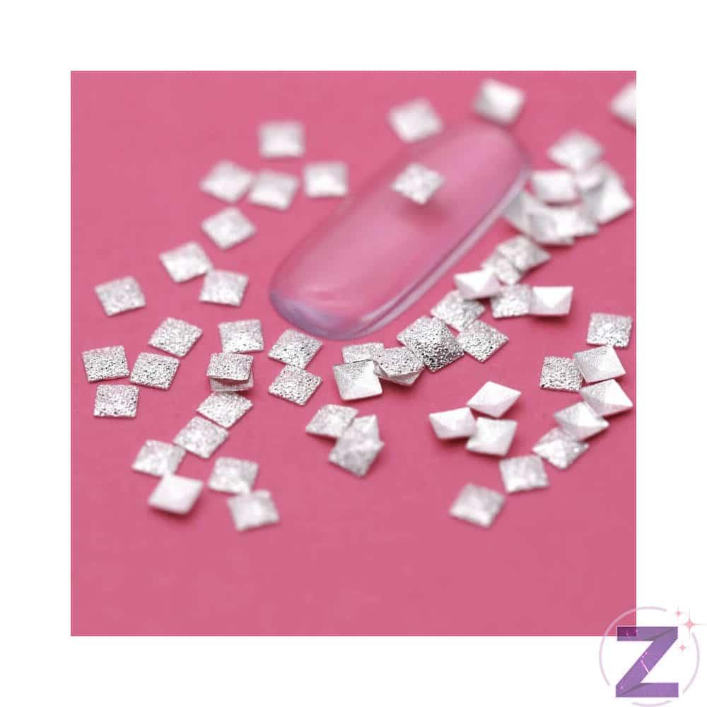 3*3mm-es ezüst négyzet körömdísz.Csillámos felületű. Dekoratív díszítőelem. 30db/cs.