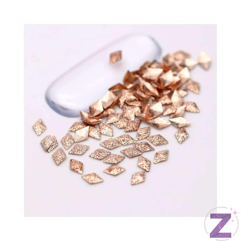 Szegecs körömdísz rombusz formában Rose Gold színben, különleges hatású csillámos felülettel. Nagyszerűen kombinálható Rose Gold színű strasszköveinkkel, szórógyöngyeinkkel.