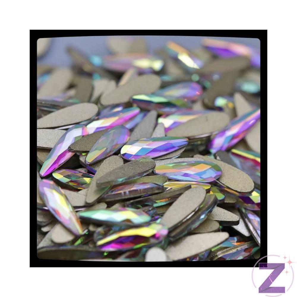 Zodiac üveg cseppforma 10*3mm-es Crystal AB színben. Színjátszó hosszúkás cseppforma. Flatback ragasztható üveg körömdísz. Különleges színjátszó színvilága egyedi külsőt kölcsönöz megjelenésének.