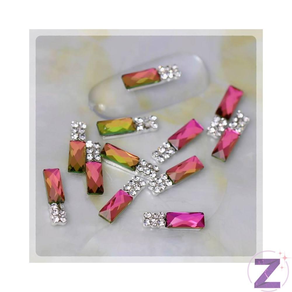 Zodiac körömékszer összetett dísz, rainbow színű hasábforma crystal színű strasszkövekkel díszítve,arany és ezüst foglalatban. Önmagában is mutatós körömékszer, izgalmas változó színvilága vonzza a tekintetet. Alja enyhén hajlított így könnyen alkalmazkodik a köröm ívéhez.