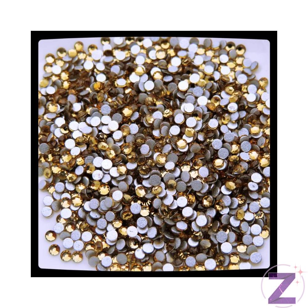 Zodiac strasszkő Light Colorado Topaz, ragasztható üveg strasszkő dekorációs díszítésekhez. Flatback no hotfix típusú, azaz ragasztható, lapos felületének köszönhetően alkalmas köröm, kreatív dekorációk, ajándéktárgyak, nagyobb méretekben pedig ruhák díszítésére. Eredetileg barna színű füstkvarc melynek lelőhelye Észak-Amerikában, Pikes Peak (Colorado) gránit-pegmatitjaiban található.
