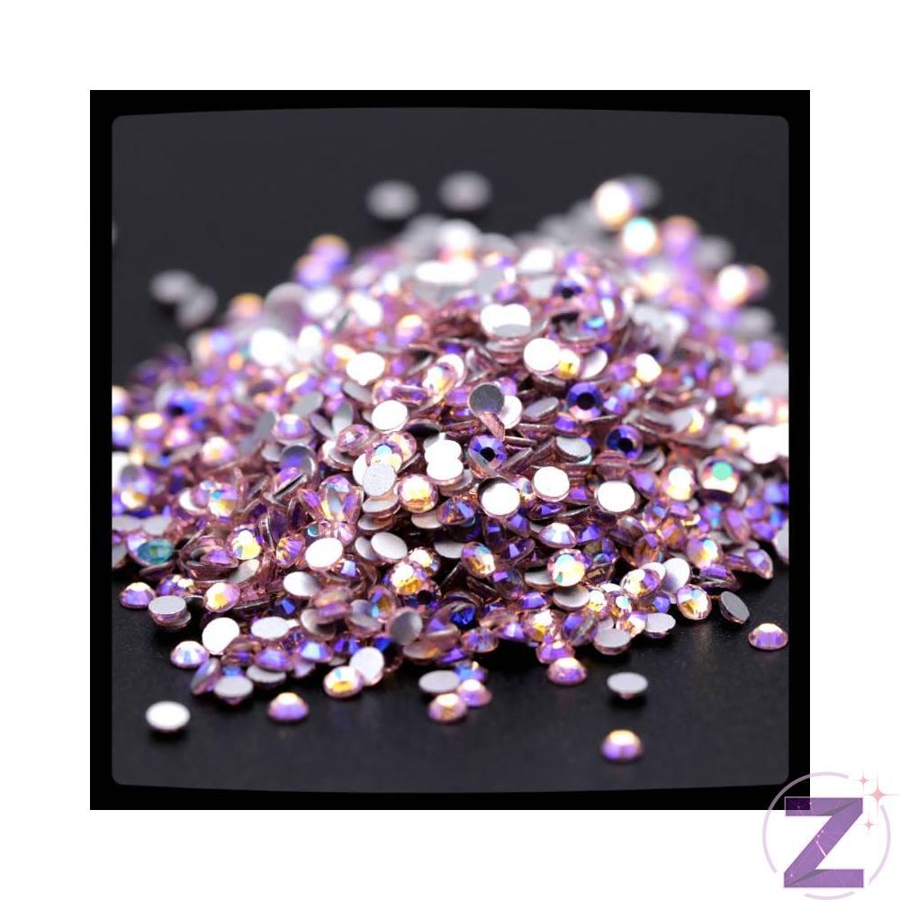 Zodiac strasszkő, Light Rose AB, ragasztható üveg strasszkő dekorációs díszítésekhez.Üde, világos rózsaszín a nőies színek kedvelőinek, fiatalosságot sugározó ragyogása vonzza a tekintetet, színpalettánk megkérdőjelezhetetlen alapja. Az alapszín színjátszó réteggel kezelve. Flatback típusú, alján fóliázott 8 oldalra csiszolt strassz.