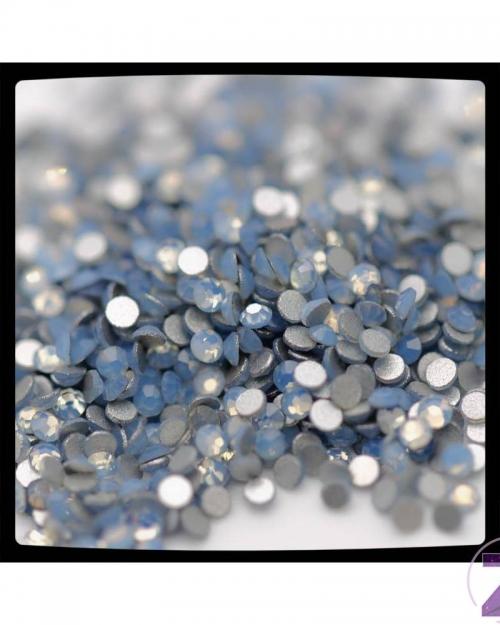 Zodiac strasszkő - Air Blue Opal színben. Manapság divatosak az opálos hatású kövek, a fehéret mindenki imádja, de izgalmasak a színek is! Az ég fátyolos kékje viselője lehet az, aki ezt a strasszkövet választja. Minden szín hangulatteremtő, érdemes kísérletezni velük! 8 fazettára csiszolt, flatback és ragasztható.
